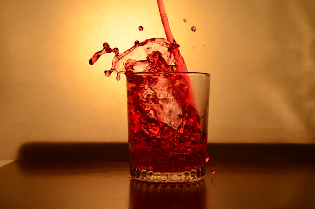 red liquid splashinging into a glass