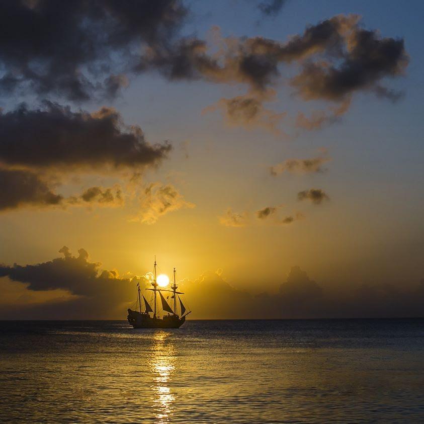 Two-mast sailing ship, little sail up, golden sunset