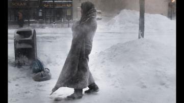 Homeless person in a thing blanket, in a windy blizzard
