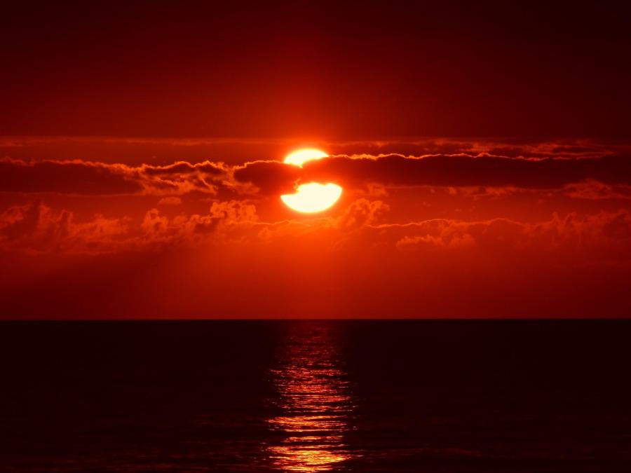 Red sunrise over ocean horizon